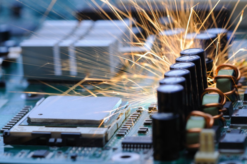 Physically inspecting a motherboard for sparks and blown capacitor.